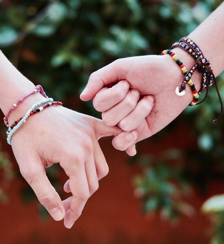 Zwei weibliche Hände umfassen ihre jeweiligen kleinen Finger - Symbolbild zu Freundschaften außerhalb der Paarbeziehung
