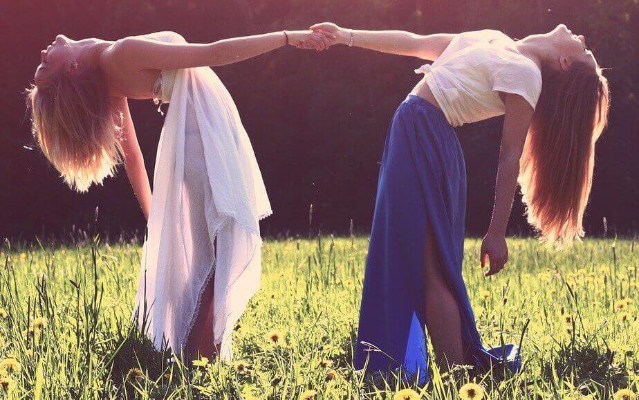 Zwei Frauen führen gemeinsam einen Tanz auf, halten sich an den Händen und beugen sich nach hinten